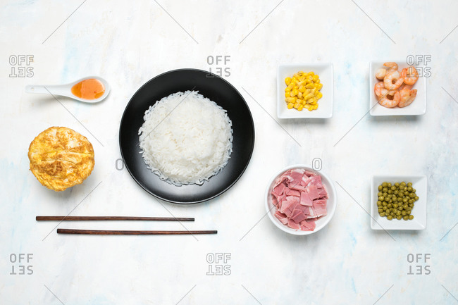 Flat lay of various delicious products for traditional Asian dish placed on white table in studio