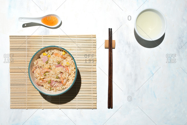Chopsticks and bowl with freshly cooked rice with prawns and vegetables
