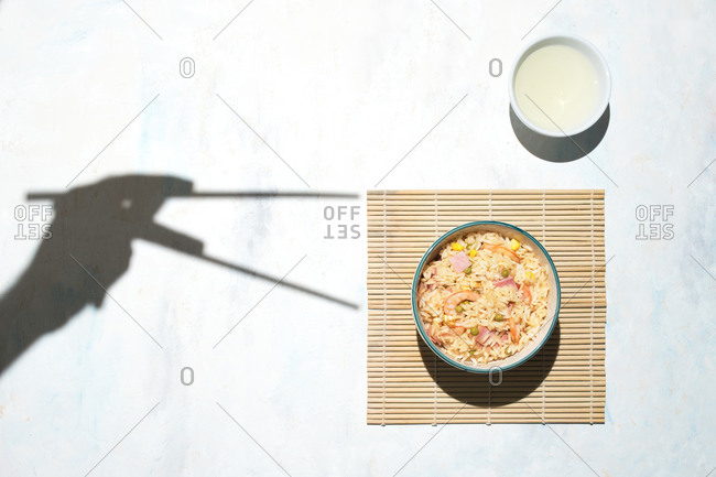 Top view of shadow of person with chopsticks and bowl with freshly cooked rice with prawns and vegetables