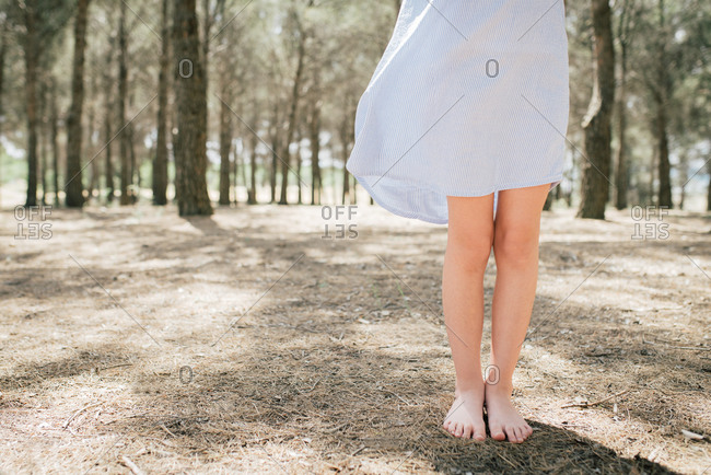 Crop unrecognizable slender barefoot child in pale blue dress standing on dry terrain in alley on sunny day in countryside