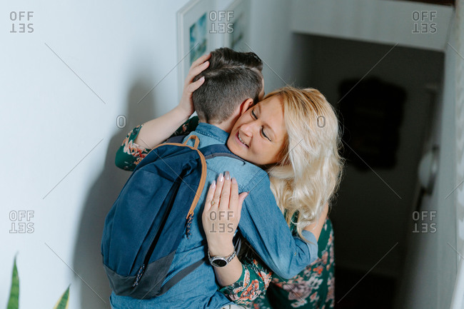 Content mother gently kissing teenage son with school backpack while hugging together on steps in cozy modern house
