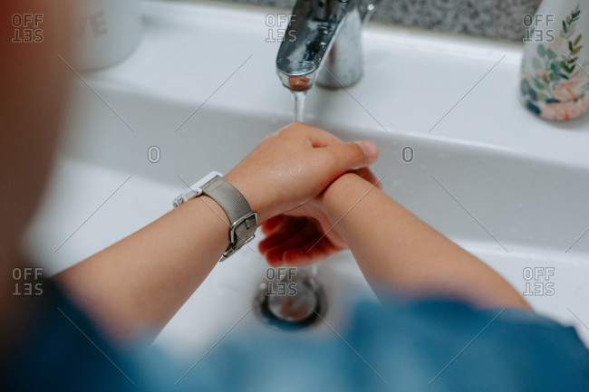 From above cropped unrecognizable little child washing hands in sink in cozy bathroom at home