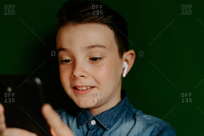 Positive smiling schoolboy wearing denim browsing modern mobile phone and listening to favorite music via wireless earbuds while standing against dark green background