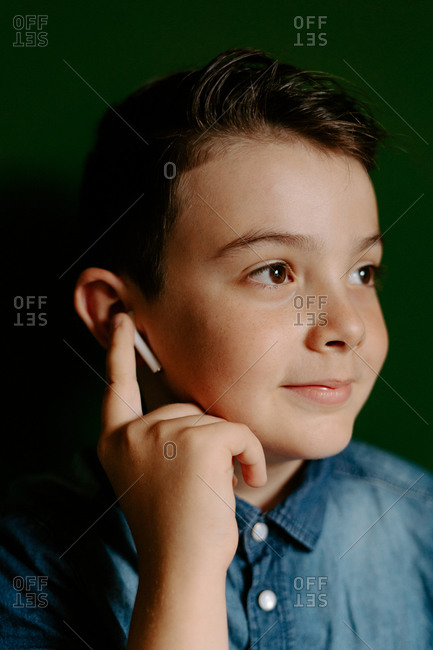 Happy schoolboy wearing denim shirt looking away while standing against dark green background listening to music on modern wireless white earbuds