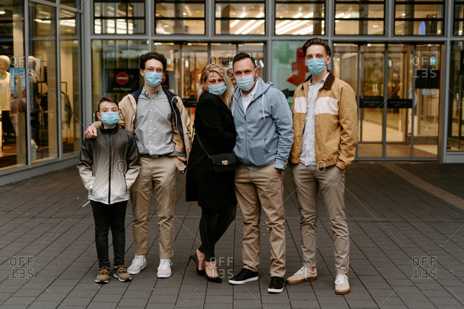 Full body content stylish relatives in warm jackets wearing protective face masks and looking at camera while standing against modern building glass door during coronavirus pandemic