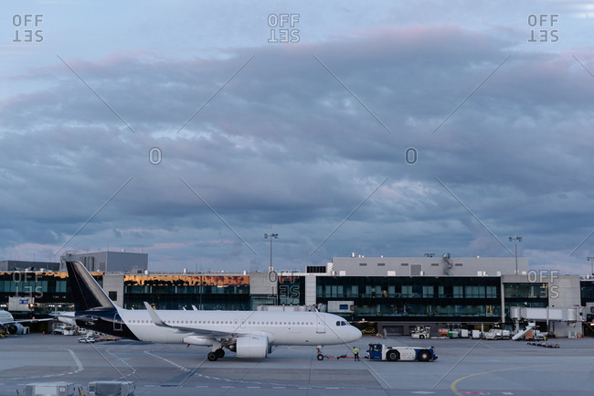 Contemporary white aircraft parked on airfield near modern glass airport terminal against picturesque cloudy dark blue sky