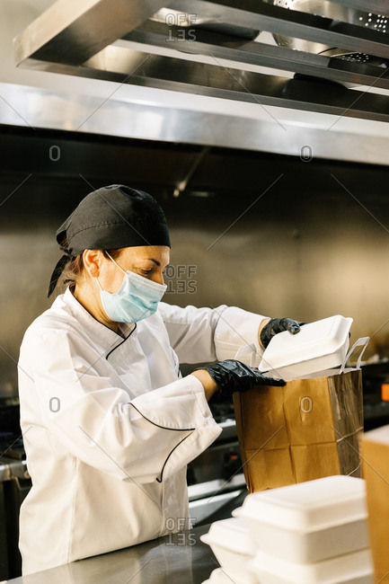 Concentrated female chef wearing face mask and uniform while working in modern restaurant kitchen and packing containers with food into paper bag for takeaway