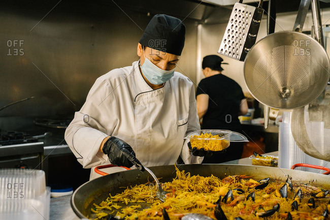 Focused female chef placing delicious noodle with seafood in plastic container for delivery while working in restaurant kitchen during coronavirus pandemic