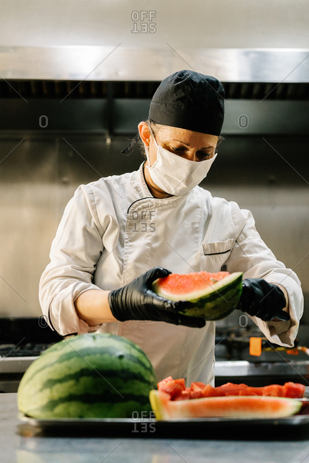 Focused female cook in uniform and face mask slicing fresh juicy watermelon while working in restaurant kitchen