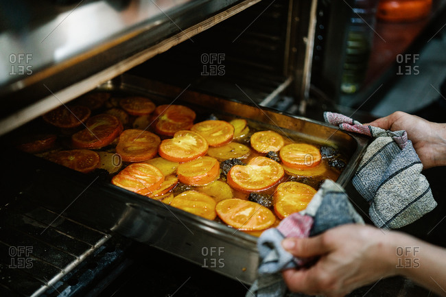 Crop unrecognizable person putting delicious vegetable casserole with potatoes and tomatoes into hot oven by using hand towels