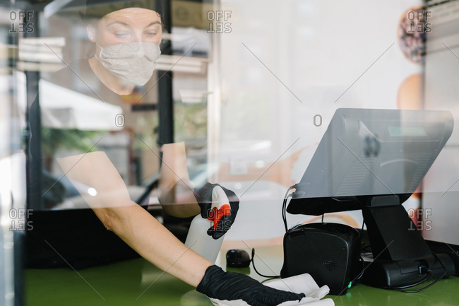 Through glass crop concentrated female cashier wearing respirator and latex gloves wiping counter with cloth while working in cafe to prevent coronavirus spreading