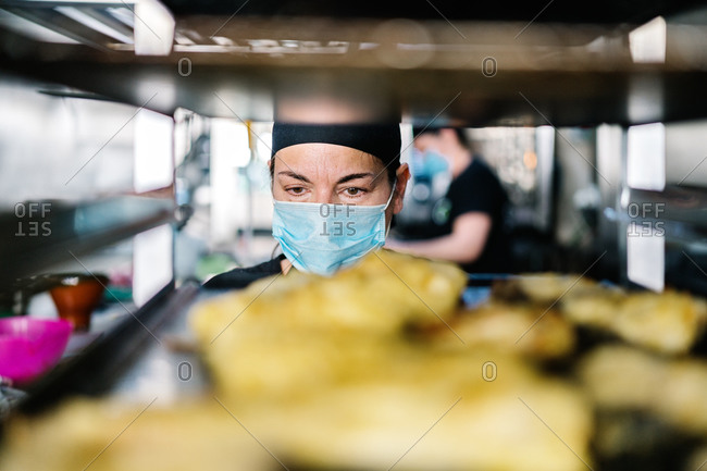 Concentrated female cook in hat and respirator standing against steel pan rack loaded with food while working in modern restaurant kitchen