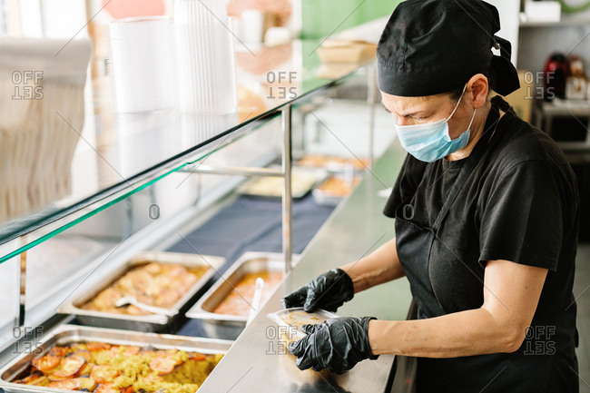 Side view o waitress in face mask putting fresh tasty dish into plastic takeaway container while working in cafe during coronavirus outbreak