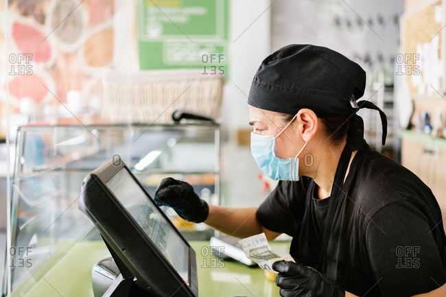 Side view serious female cashier wearing gloves and mask tapping on cash register touchscreen during duty in contemporary cafe