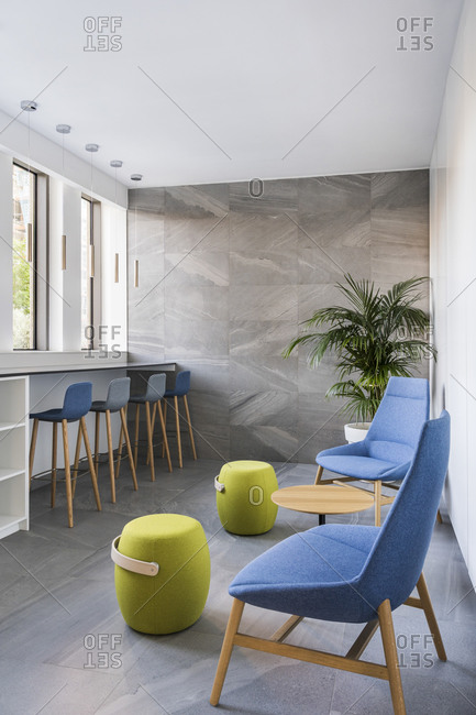 Modern bright interior with high ceilings furnished with design lamps, chairs, stools and a plant. Light coming from windows