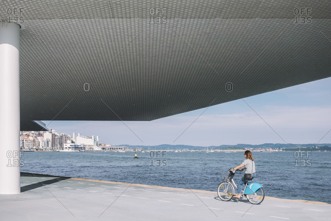 Side view of female in casual wear riding bike near modern building and waterfront during sunny day