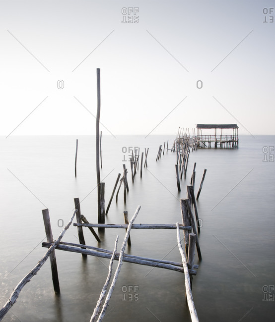 Abandoned partially destroyed dock made of thick wooden sticks on endless ocean with pure water under serene sky in daylight