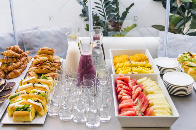 High angle of assorted smoothie in glass bottles an tasty sandwiches with slices of bacon and sweet croissants placed on table with empty glasses for party