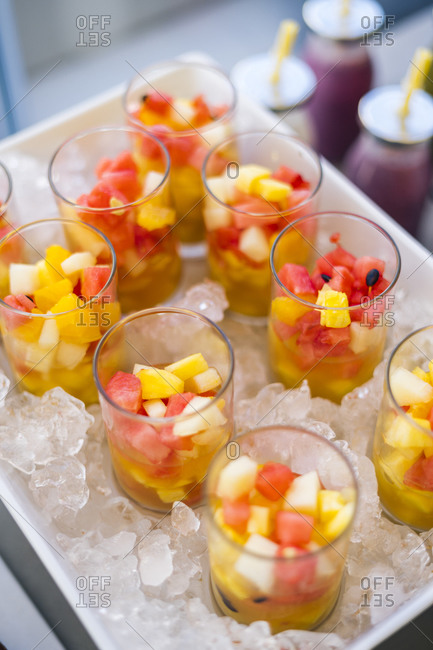 High angle of glasses with refreshing fruit salad made with assorted colorful fruits served on tray with ice