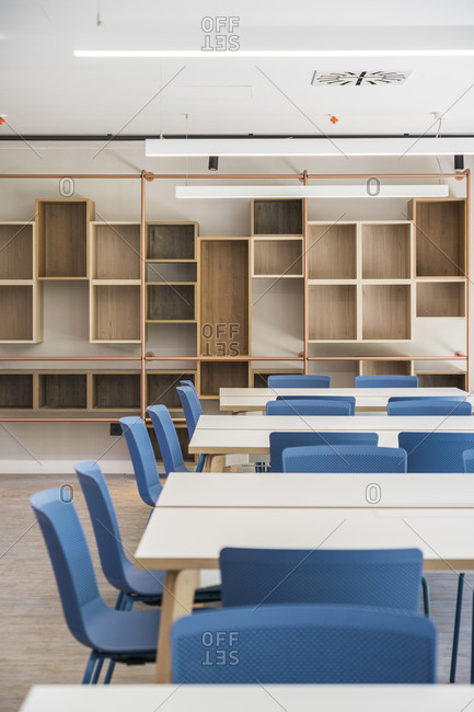 Modern style office interior with square tables and blue stools on floor and wooden shelves on wall with large window and lamps on ceiling