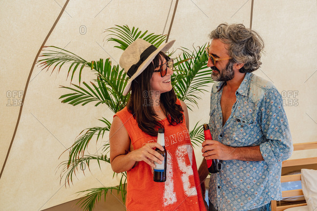Delighted smiling couple wearing casual summer clothes standing with bottles of beer and bonding in luxury resort tent