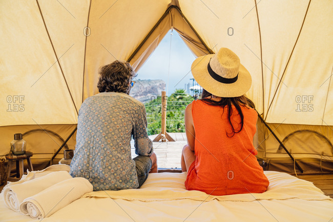 Full length happy mature couple in casual summer wear sitting on bed in luxury camping resort and looking away with tenderness