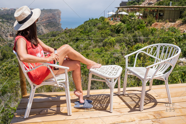 Side view full body faceless relaxed female in hat sitting gracefully on cane chair with bottle of beer and looking at wonderful scenery of rocky cliffs and green tropical foliage