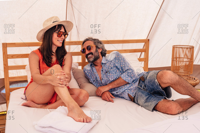 Full length happy mature couple in casual summer wear sitting on bed in luxury camping resort and looking at each other with tenderness
