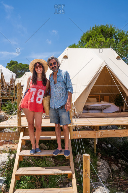 Full length smiling couple in casual outfits standing on wooden staircase leading to cozy camping tent in tropical resort while bonding and looking at camera happily