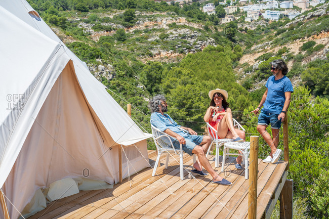 Full length mature friends chilling on sunny terrace near camping tent against picturesque landscape of green tropical highlands