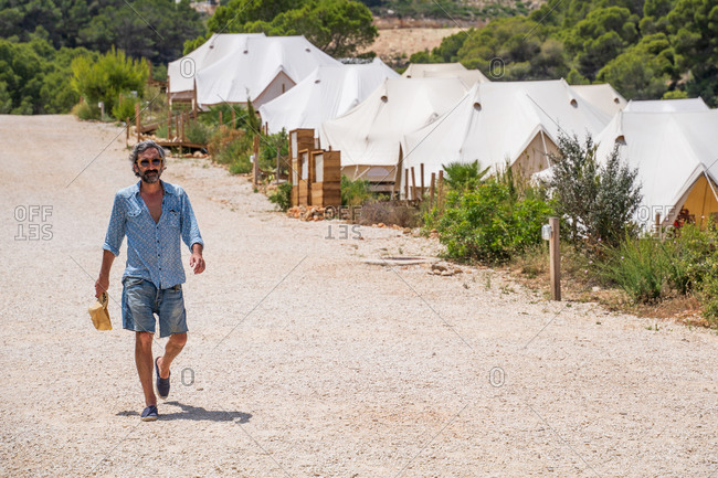 Full length relaxed confident mature male in casual outfit and sunglasses walking along rural gravel road nearby luxury resort camping complex during hot summer day