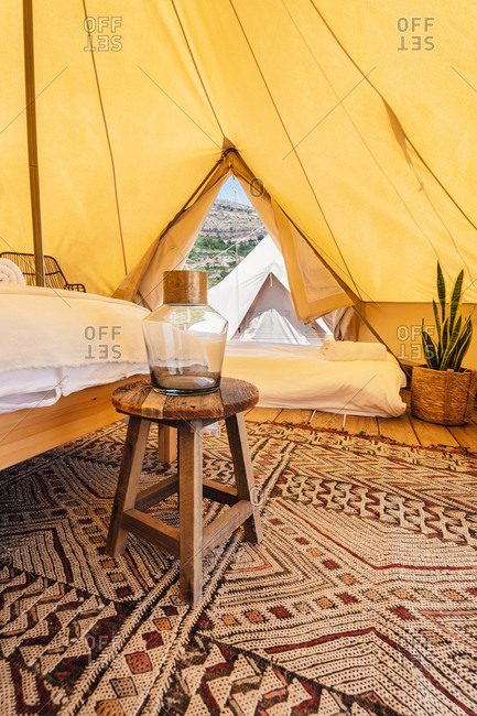 Amazing interior design of spacious cozy camping tent with comfy beds and creative lamps placed on carpet in tropical resort