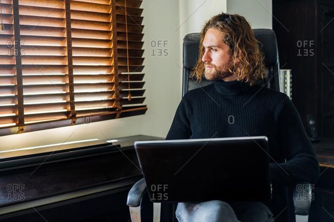 Handsome man working at desktop computer at home
