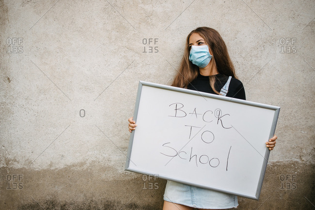 Girl wearing a mask holding a whiteboard that has back to school written on it.