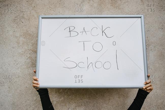 Hands holding whiteboard that has back to school written on it