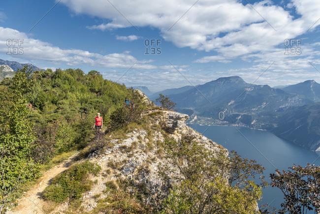 Pregasina, Riva del Garda, Trento Province, Trentino, Italy. Hikers on the climb to Punta Larici high above Lake Garda