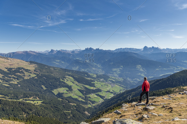 Latzfons, Klausen, Bolzano province, South Tyrol, Italy, Europe. A hiker admires the mountain panorama from Jocherer Berg. In the background the Dolomites