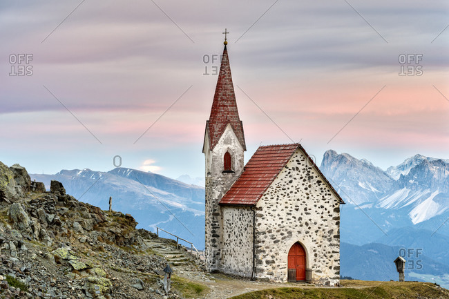 Latzfons, Klausen, Bolzano province, South Tyrol, Italy, Europe. The pilgrimage church Latzfonser Kreuz after sunset with a view of the Dolomites with the Peitlerkofel