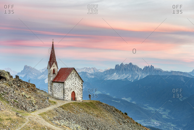 Latzfons, Klausen, Bolzano province, South Tyrol, Italy, Europe. The pilgrimage church Latzfonser Kreuz after sunset with a view of the Dolomites with the Peitlerkofel and the Geisler peaks