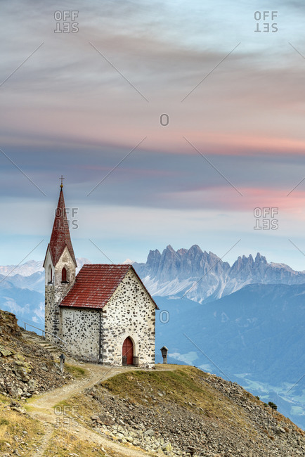 Latzfons, Klausen, Bolzano province, South Tyrol, Italy, Europe. The pilgrimage church Latzfonser Kreuz after sunset with a view of the Dolomites with the Odle peaks