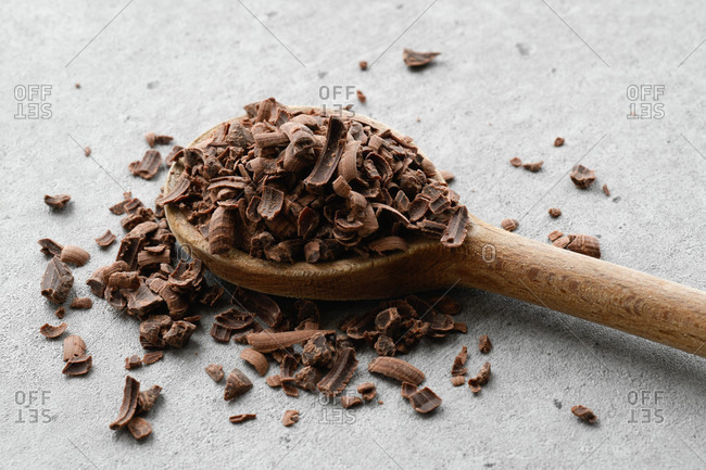 Wooden spoon full of grated milk chocolate