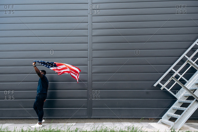 Afro American man in stylish casual clothes waves the USA flag near a black wall outdoors