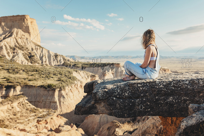 Woman sitting on cliff overlooking beautiful canyons