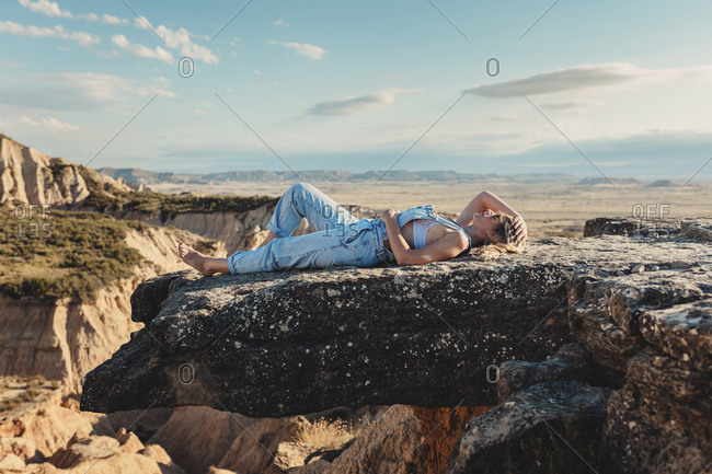 Woman lying down on cliff surrounded by beautiful canyons