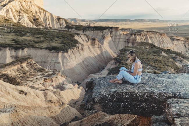 Blonde woman sitting on a cliff overlooking beautiful canyons
