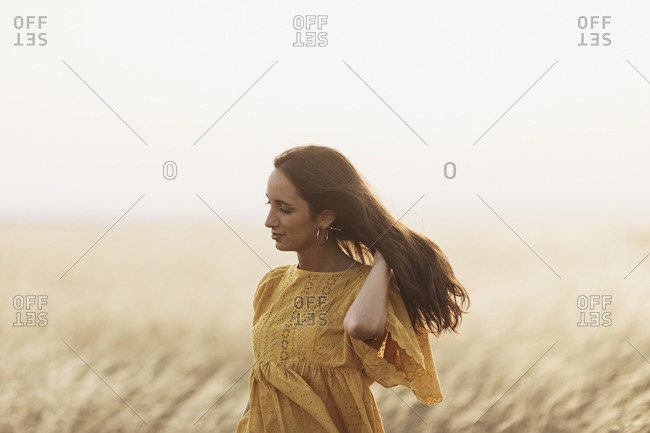 Woman with long dark hair standing in a wheat field at sunset