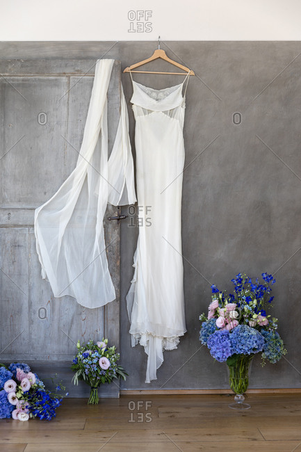 White bridal dress and veil hanging on gray wall near bunches of flowers prepared for wedding anniversary celebration