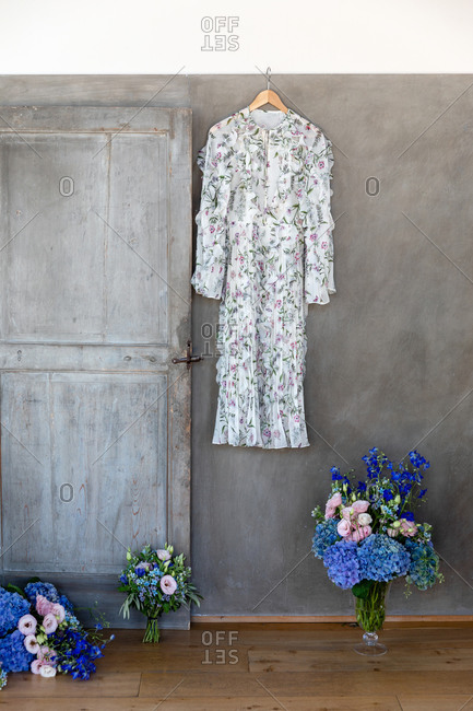 Stylish dress with floral ornament hanging on gray wall near bouquets of fresh flowers prepared for holiday celebration