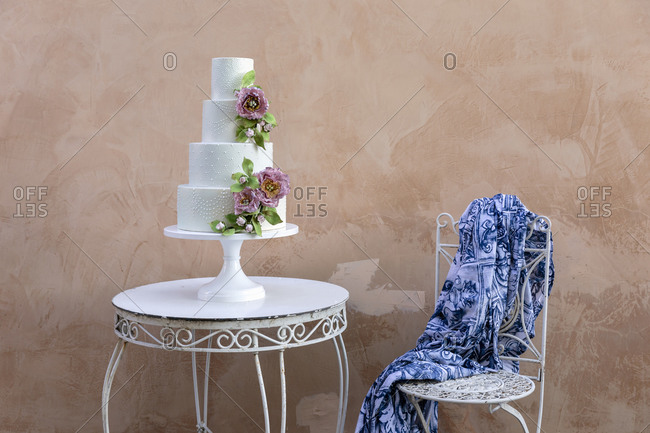 Fancy tiered wedding cake decorated with flowers and placed on table near chair with ornamental shawl against beige wall