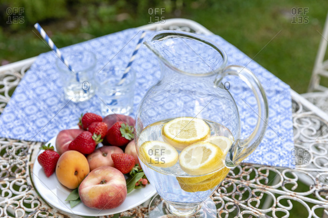 From above glass jug of natural lemonade and plate with ripe fruits placed on table during holiday celebration in garden